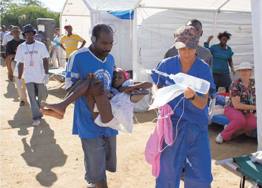 A severely dehydrated patient receives iv fluids from Kari Jones, MD, as she is carried by a family member from triage to a tent at the Bercy CTC. Photo courtesy of Samaritan's Purse.